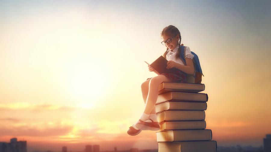 Pige der sidder på en bunke bøger