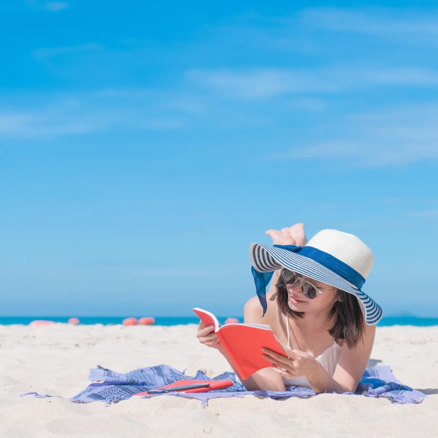 Foto: Kvinde på strand læser en bog