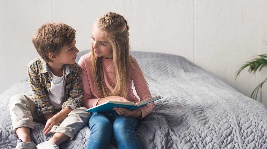 To børn der læser på en seng