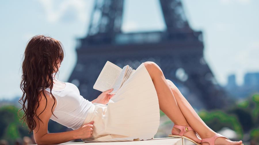 Kvinde der læser ved Eiffeltårnet
