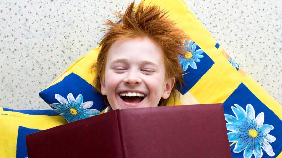 Foto: Dreng læser bog og griner