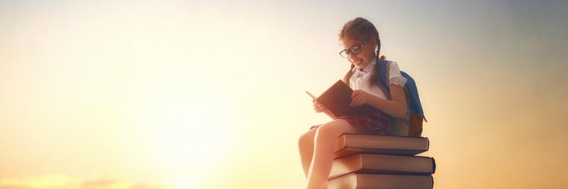 En pige der sidder på en bunke bøger
